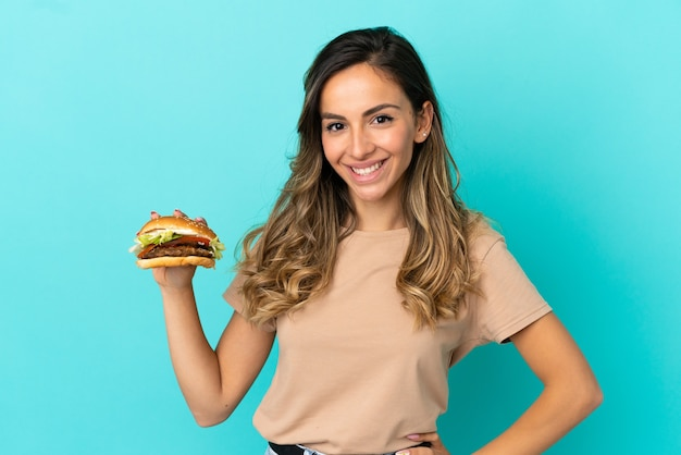 Młoda kobieta trzymająca burgera na białym tle, pozująca z rękami na biodrach i uśmiechnięta