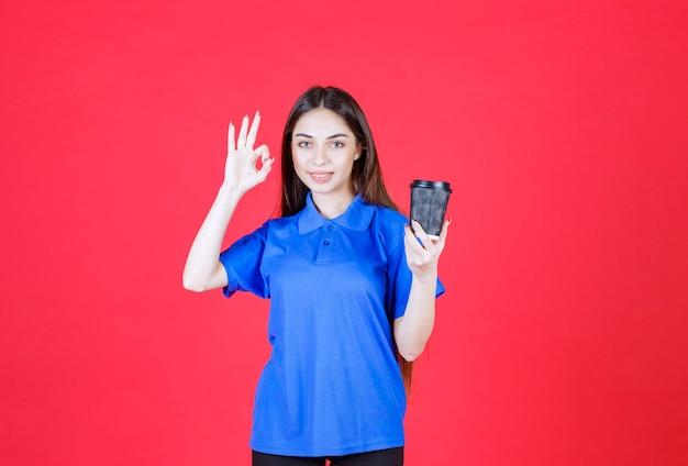 Młoda kobieta trzymająca czarną jednorazową filiżankę kawy i pokazująca pozytywny znak ręki