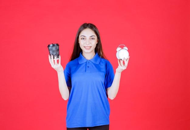 Młoda kobieta trzymająca czarną jednorazową filiżankę napoju i budzik