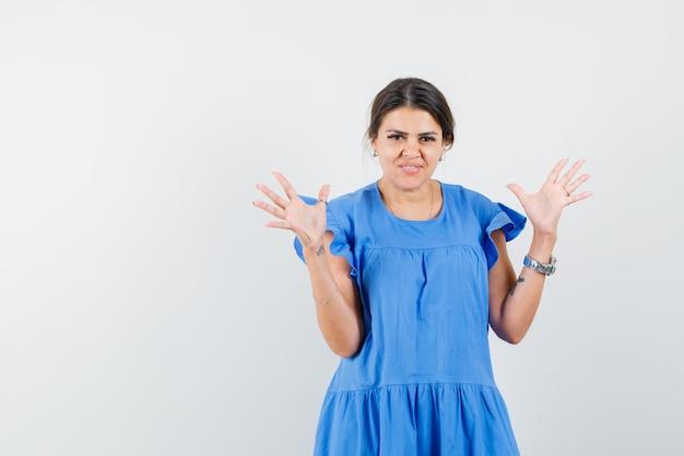 Młoda kobieta trzymająca dłonie podniesione w niebieskiej sukience i wyglądająca na szczęśliwą