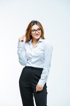 Młoda kobieta trzymająca długopis, odwracając wzrok