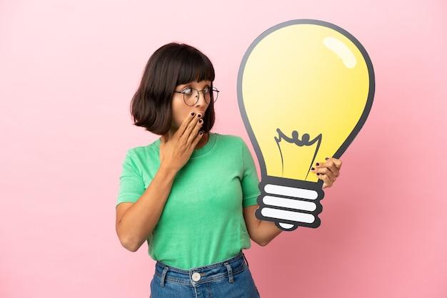 Młoda kobieta trzymająca ikonę żarówki ze zdziwionym wyrazem twarzy