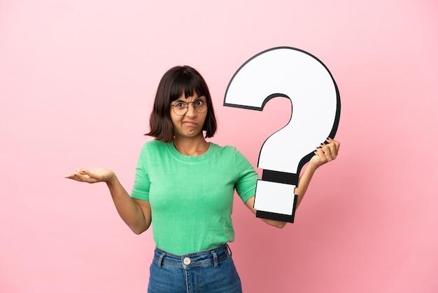 Młoda kobieta trzymająca ikonę znaku zapytania i mająca wątpliwości