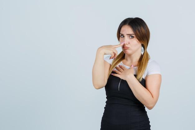 Młoda kobieta trzymająca jedną rękę nad klatką piersiową, kładąc palec wskazujący na nosie