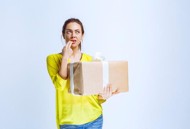 Młoda kobieta trzymająca kartonowe pudełko i myśląca o nieznanym nadawcy