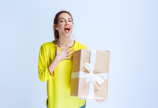 Młoda kobieta trzymająca kartonowe pudełko i wskazująca na siebie