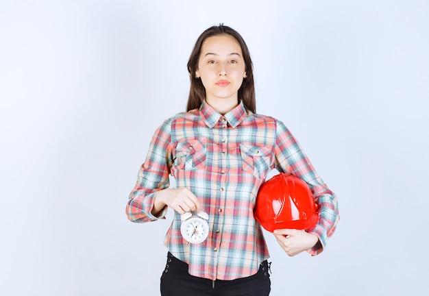 Młoda kobieta trzymająca kask i budzik.