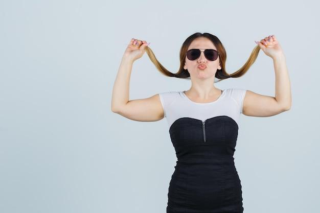 Młoda kobieta trzymająca kosmyk włosów podczas wysyłania pocałunku