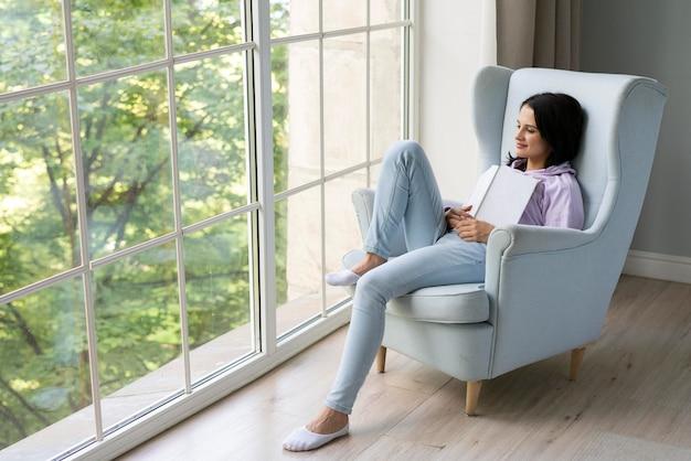 Młoda kobieta trzymająca książkę, patrząc przez okno