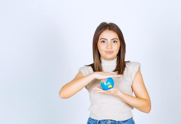 Młoda kobieta trzymająca kulę kuli ziemskiej