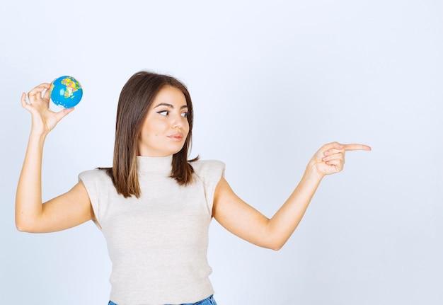 Młoda kobieta trzymająca kulę ziemską i wskazującą palcem wskazującym