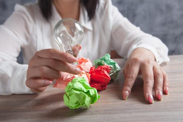 Młoda kobieta trzymająca lampę i zmięte papiery