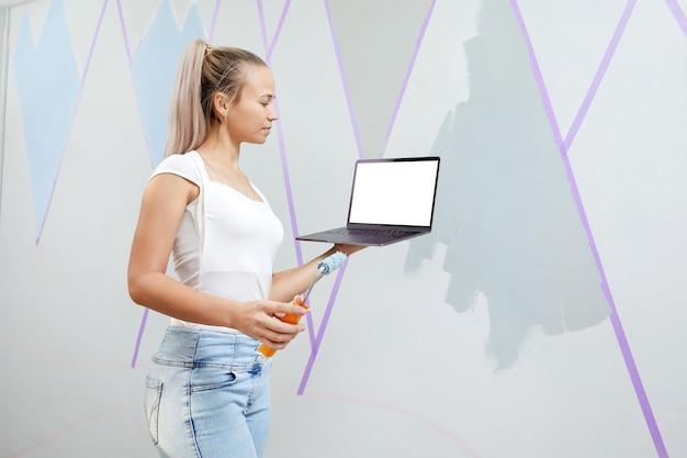 Młoda kobieta trzymająca laptopa z pustym białym ekranem do malowania ścian za pomocą wałka do malowania