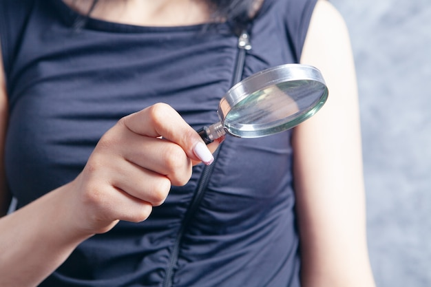 Młoda kobieta trzymająca lupę