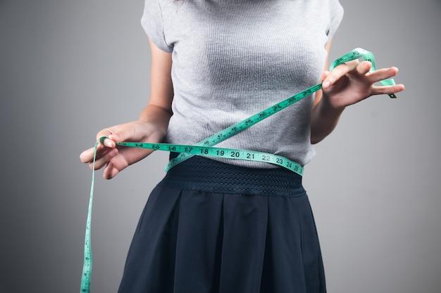 Młoda kobieta trzymająca metry w talii