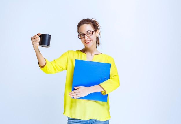 Młoda kobieta trzymająca niebieską teczkę i czarną filiżankę napoju