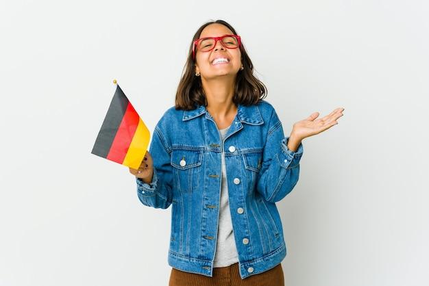 Młoda kobieta trzymająca niemiecką flagę śmieje się głośno, trzymając rękę na piersi