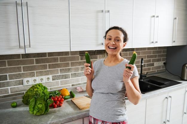 Młoda kobieta trzymająca ogórki w dłoniach i uśmiechnięta z zębatym uśmiechem, patrząc w kamerę, stojąca naprzeciw kuchni w domu