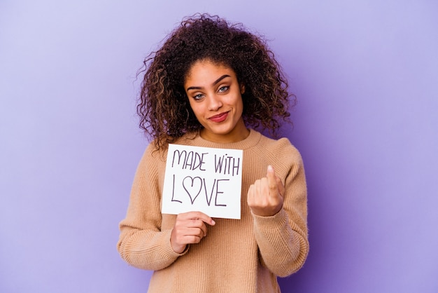 Młoda kobieta trzymająca plakietkę made with love na fioletowej ścianie wskazująca palcem na ciebie, jakby zapraszająca, podeszła bliżej