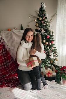 Młoda kobieta trzymająca prezent i przytulająca córkę przed choinką sylwestrową