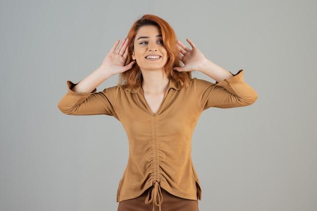 Młoda kobieta trzymająca ręce w górze i uśmiechająca się na szarej ścianie