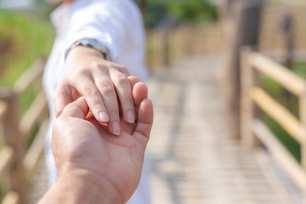 Młoda kobieta trzymająca rękę mężczyzny prowadząca go po ogrodzie kwiatowym