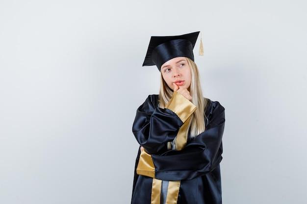 Młoda kobieta trzymająca rękę na brodzie w mundurze absolwenta i patrząca z wahaniem