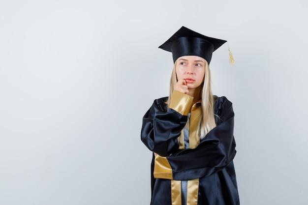 Młoda kobieta trzymająca rękę na brodzie w mundurze absolwenta i wyglądająca na zamyśloną