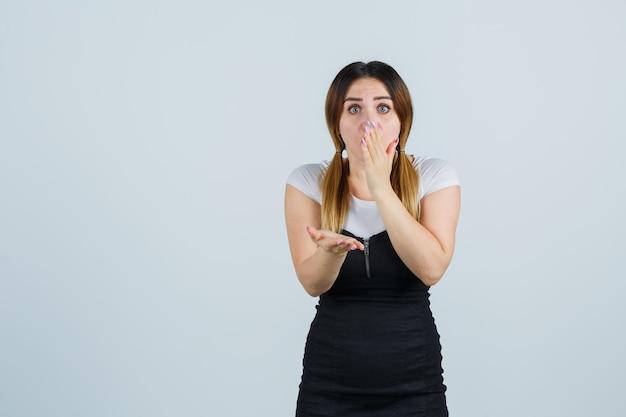 Młoda kobieta trzymająca rękę na ustach i wyglądająca na zdziwioną
