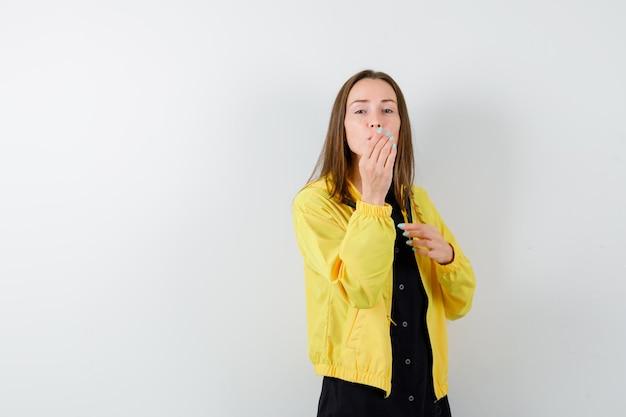 Młoda kobieta trzymająca rękę na ustach i wysyłająca buziaki