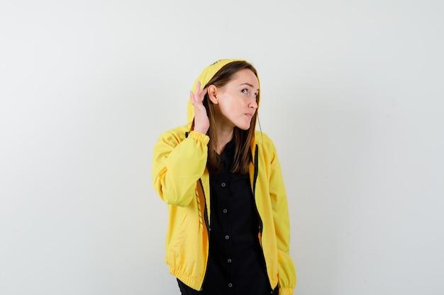 Młoda kobieta trzymająca rękę przy uchu, aby coś usłyszeć