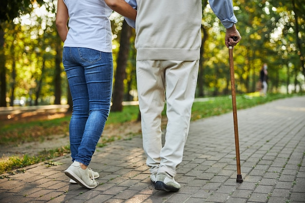 Młoda kobieta trzymająca rękę starszego mężczyzny na ulicy
