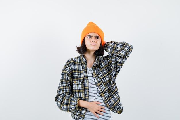 Młoda kobieta trzymająca rękę za głową w pomarańczowym kapeluszu w kratkę, wyglądająca na zdziwioną