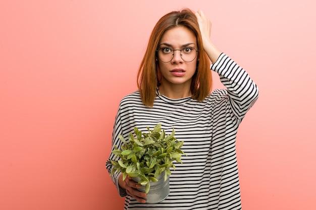 Młoda kobieta trzymająca roślinę w szoku, przypomniała sobie ważne spotkanie.