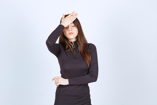 Młoda kobieta trzymająca się za głowę, gdy boli ją głowa lub była podekscytowana