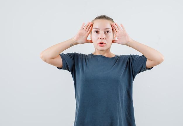 Młoda kobieta trzymająca się za ręce, aby wyraźnie zobaczyć w szarej koszulce i wyglądająca na zdumioną