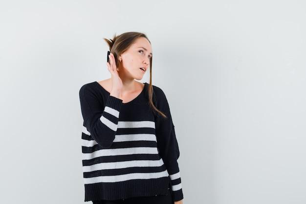 Młoda Kobieta Trzymająca Się Za Ręce Blisko Ucha, Próbująca Usłyszeć Coś W Dzianinie W Paski I Czarnych Spodniach I Wyglądająca Na Skupioną Darmowe Zdjęcia