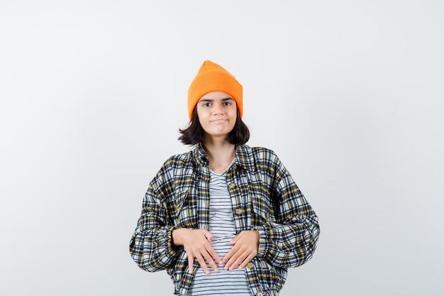 Młoda kobieta trzymająca się za ręce na brzuchu w pomarańczowym kapeluszu wygląda na zadowoloną