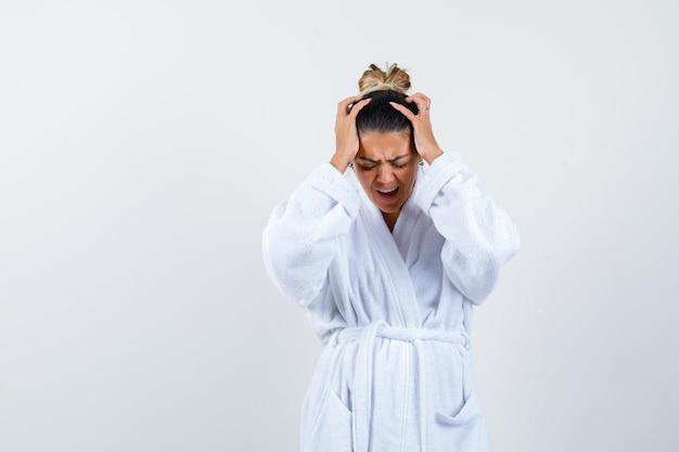 Młoda kobieta trzymająca się za ręce na głowie w szlafroku i wyglądająca na zdezorientowaną