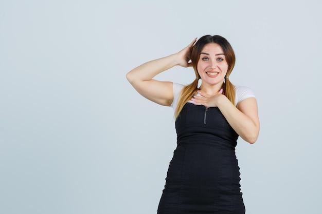 Młoda kobieta trzymająca się za ręce na klatce piersiowej i głowie
