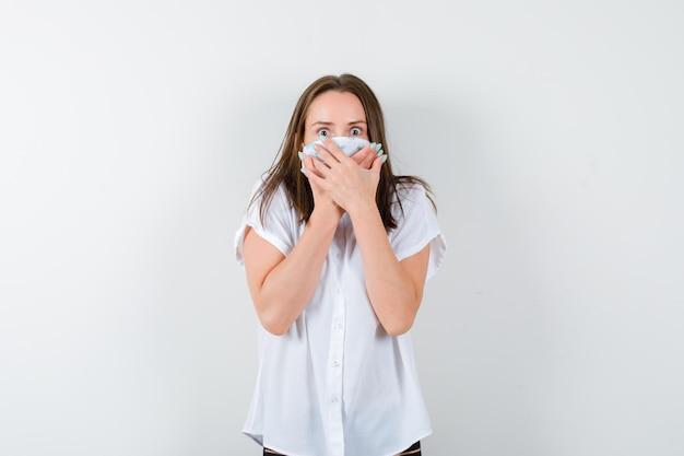 Młoda kobieta trzymająca się za ręce na ustach i wyglądająca na przestraszoną