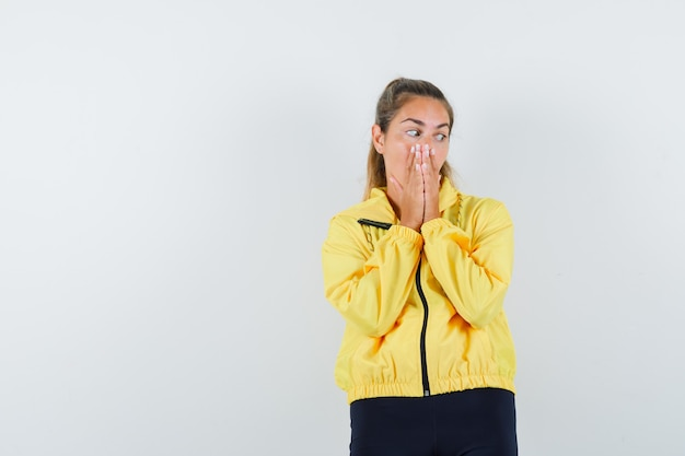 Młoda kobieta trzymająca się za ręce, patrząc w bok w żółtej bomberce i czarnych spodniach, patrząc zamyślony