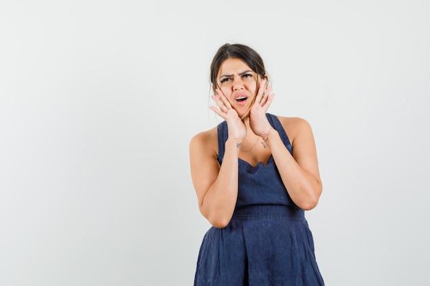 Młoda kobieta trzymająca się za ręce przy ustach w sukience i wyglądająca na niezadowoloną