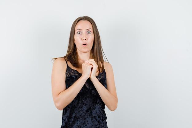 Młoda kobieta trzymająca się za ręce splecione w czarny podkoszulek i wyglądająca na przestraszoną.