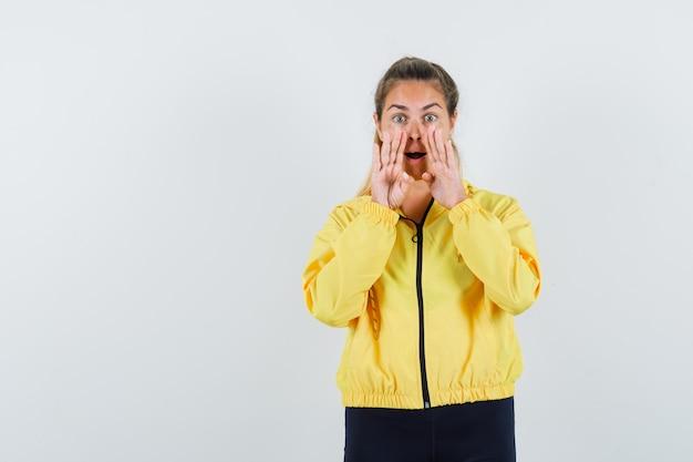 Młoda kobieta trzymająca się za ręce w pobliżu ust, dzwoniąc do kogoś w żółtej bomberce i czarnych spodniach i wyglądająca uroczo