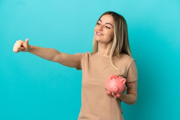 Młoda kobieta trzymająca skarbonkę nad odosobnionym niebieskim tłem, pokazująca gest kciuka w górę