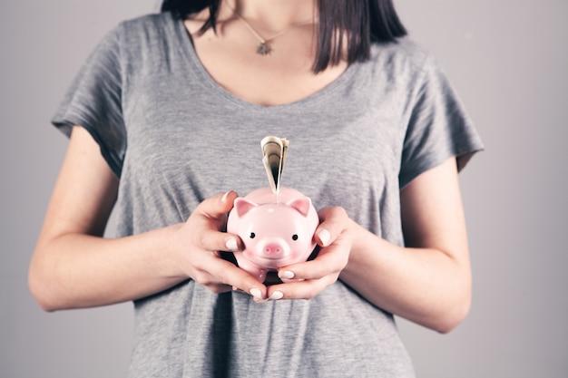 Młoda kobieta trzymająca skarbonkę z banknotem dolarowym