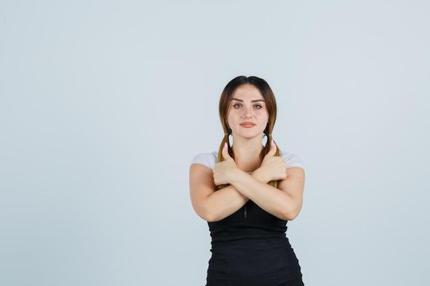 Młoda kobieta trzymająca skrzyżowane ręce i pokazująca podwójne kciuki w górę