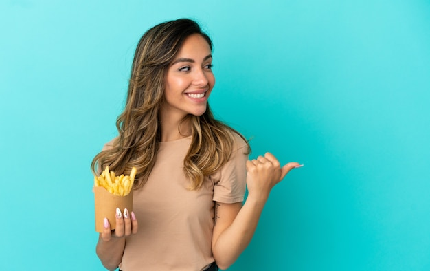 Młoda kobieta trzymająca smażone frytki na białym tle, wskazująca na bok, aby zaprezentować produkt