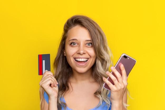 Młoda kobieta trzymająca w dłoni plastikową kartę kredytową i telefon komórkowy, aby zapłacić za zakupy online